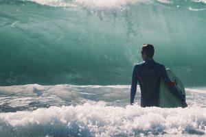 guy-walking-towards-waves